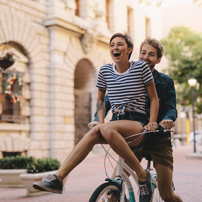 Young couple riding a bike outside