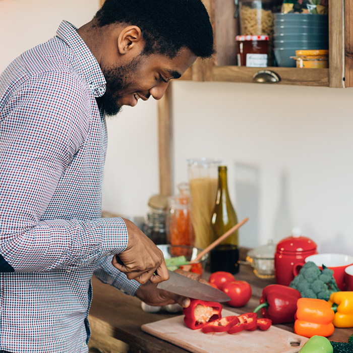 Young man chopping vegetables in kitchen
